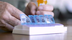 An man in his 70s fills his weekly pill planner with his medicine for the week - stock footage