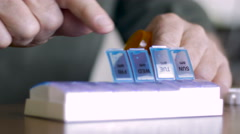 A man closes his weekly pill dispenser after filling it with his medicine - CU Stock Footage