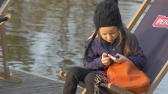 Kid is Sitting in Deck Chair and Play Phone Blonde Girl Resting on Pier Calm Stock Footage