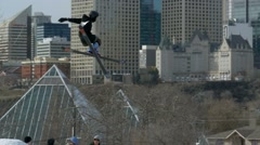 Skier big air grab with city skyline in background - stock footage
