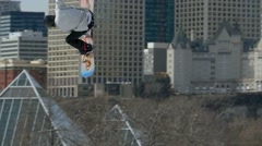 Snowboarder 540 big air grab with city skyline in background - stock footage