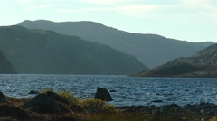 A small mountain lake with a rocky shore. Stock Footage