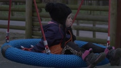 Kid is Sitting on a Nest Swing and Swaying Daughter is Playing on a Swing in a Stock Footage