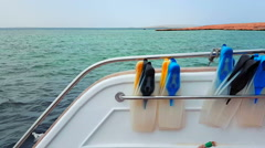 Flippers on the stern of the yacht in the azure lagoon - stock footage