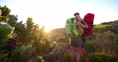 Rearview of hiking Couple hugging and watching sunrise in nature Stock Footage