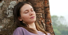 Young woman asleep leaning against a tree Stock Footage