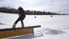 Snowboarder does rail slide to 180 during contest - stock footage