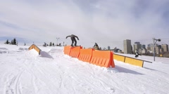Snowboarder does 180 rail slide over steps - stock footage