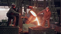 Workers on steel plant operates with molten metal Stock Footage