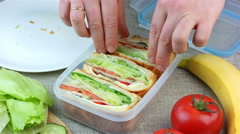 Woman made sandwiches and putting them into the lunch box Stock Footage