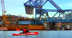 4K Woman Paddles her Kayak up to the Johnson Street Bridge in Victoria BC Stock Footage