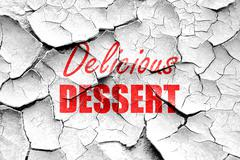 Grunge cracked Delicious dessert sign - stock illustration