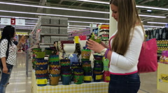 Young woman chooses a flower pot in a supermarket. In the background a woman Stock Footage