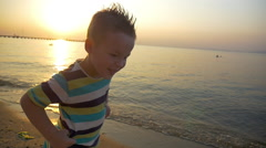 Child making angry face on the beach at sunset Stock Footage