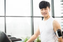Young handsome asian man works out in modern gynm Stock Photos