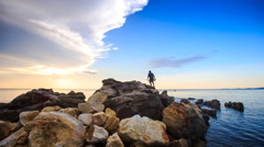 Backside Guy with Rods Walks on Stones to Sea at Sunset - stock footage