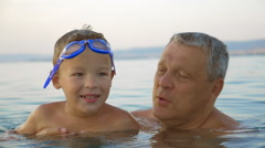Child and grandfather bathing in the sea Stock Footage