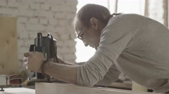 Stock Video Footage of Woodworker treats edge of wooden board by plunge router. Cut his finger