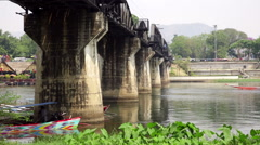 River Kwai concrete pillars with river boats Stock Footage