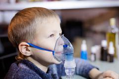 Litle boy sitting with nebulizer Stock Photos