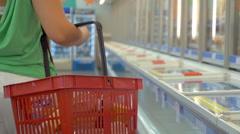 Woman walking in fridge section of supermarket Stock Footage