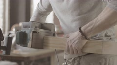 Woodworker treats edge of wooden board by belt sander. Manufacturer Stock Footage
