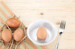 Fresh eggs on thatch and one egg in bowl with fork ,on wood background. - stock photo
