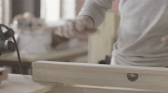 Woodworker treats edge prepared wooden board by polishing machine. Manufacturer Stock Footage