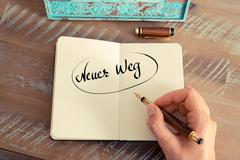 Handwritten text in German Neuer Weg - translation : New Way - stock photo