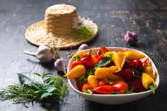 beautiful rural still life of collection peppers in plate, garlics, different - stock photo