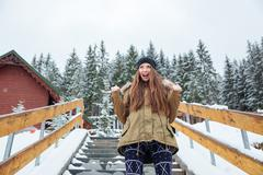 Happy excited young woman standing and shouting  in winter forest - stock photo