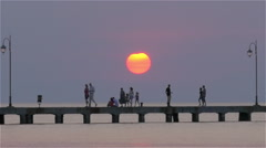 Ferry sailing by the pier with people at sunset - stock footage
