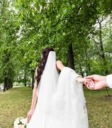 Beautiful young woman bride holds the hand of a man in outdoors. Follow me Stock Photos