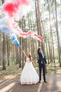 Wedding couple with color smoke in the summer park. Colour bomb - stock photo