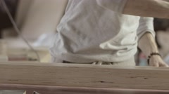 Woodworker dye long wooden board by varnish. Roller. Manufacturer. Treatment - stock footage