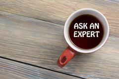 Ask an expert. Coffee cup with message. Office desk table top view Stock Photos