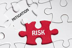 Risk Mitigation. Missing jigsaw puzzle pieces with text - stock photo