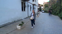 A young woman with a bag on his shoulder walks along the old European street at Stock Footage