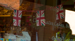 Shoppers Walk Past Quaint Shop Front Hanging Union Jack Bunting Stock Footage