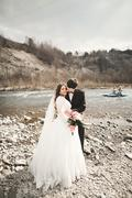 Stock Photo of Happy wedding couple, bride and groom posing neat river against backdrop of the