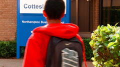 Student Wearing red Jumper Walks into Business School - stock footage