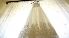 Close up of a fashionable wedding dress on a hanger , white shoes on the floor Stock Footage
