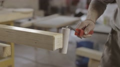 Carpenter varnishing edgee of wooden board by paint roller. Process of treatment Stock Footage
