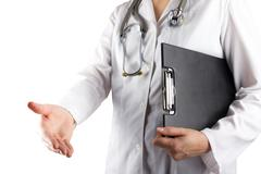 Female doctor's hand holding stethoscope and clipboard isolated on white - stock photo