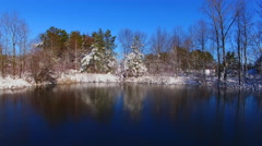 On thin ice of frozen scenic lake with snow covered trees - stock footage