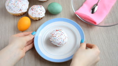 Hands take away from the table a plate with a Easter cake with white icing. Stock Footage