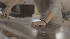 Stock Video Footage of Woodworker scratch surface of wooden board by scraper handware. Manufacturer
