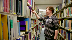 Student Looking Through Books in a Library Stock Footage