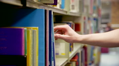 Close on Hand Picking through Library Books Stock Footage
