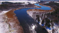 Aerial flyover of winding, icy Ahnapee River near Algoma Wisconsin Stock Footage